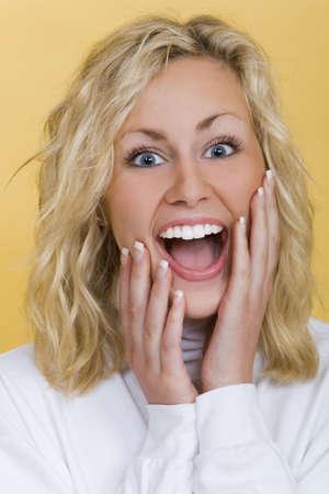 blonde yeux bleus: Le studio a tir� la belle jeune femme blonde regardant heureusement �tonnante Banque d'images