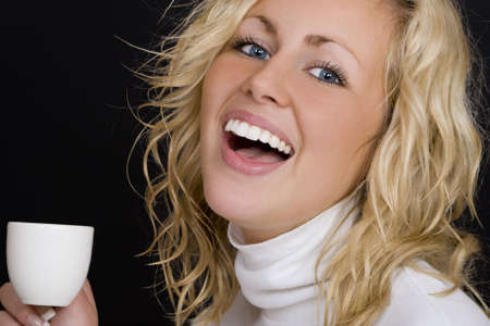 Studio shot on a black background beautiful young blond woman wearing white, laughing and drinking coffee.  Stock Photo