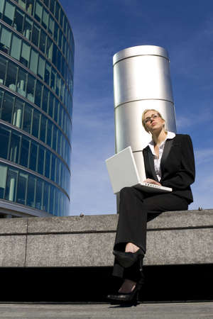 A beautiful young female executive using her laptop in a hi-tech business environment photo