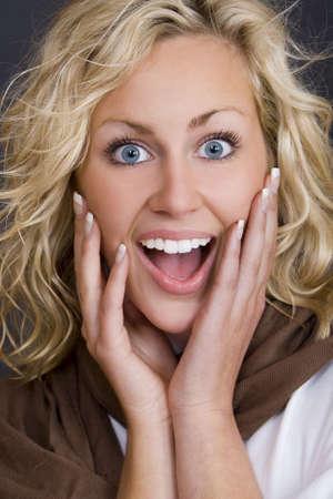 bionda occhi azzurri: Studio shot bella giovane donna bionda che indossa cercando felicemente sorpreso