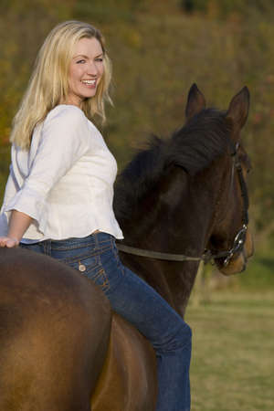 An attractive young woman riding a horse bareback during the fall Stock Photo