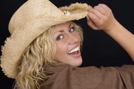 cappello cowboy: Studio tiro di un bel giovane donna con gli occhi blu brillante che indossa un cappello di paglia cowboy e ridere
