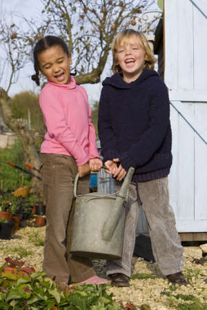 person outside: Two young children carrying a heavy watering can in an Autumnal garden