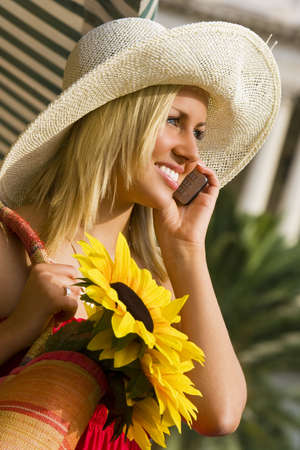 A beautiful young woman bathed in sunshine and making a call on her cell phone photo