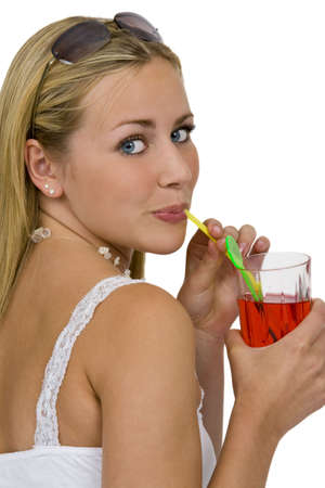 Isolated studio shot of a beautiful young woman drinking a bright red drink through a straw photo