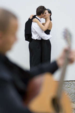 A young loving couple embrace while a street musician plays his guitar (out of focus) in the foreground photo