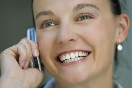 dark haired woman: A beautiful dark haired woman talks happily on her mobile phone.