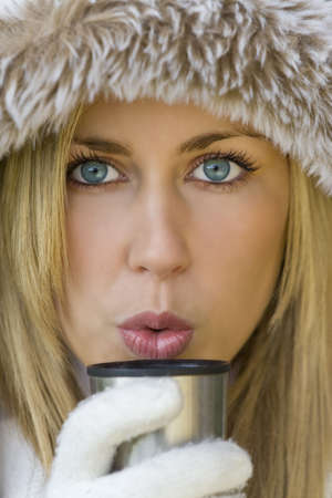 A stunningly beautiful young blond woman wrapped up warm and blowing onto a warm drink photo