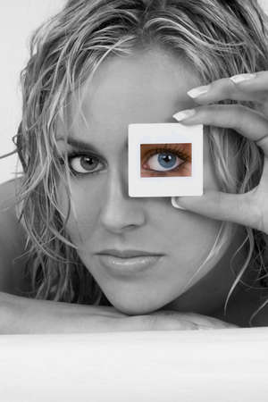 french model: Black and white studio shot of a  stunningly beautiful young blond woman with her bright blue eye looking through a transparency frame