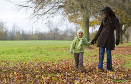 A young mixed race girl walking through the autumn leaves with her black mother Stock Photo