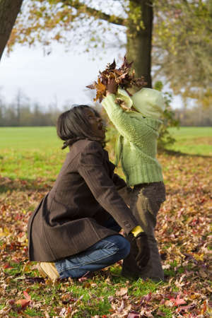fall fun: A young mixed race girl playing in the autumn leaves with her black mother