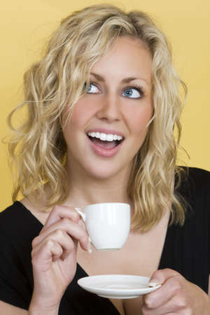 Studio shot of a beautiful young blonde woman drinking teacoffee and laughing photo