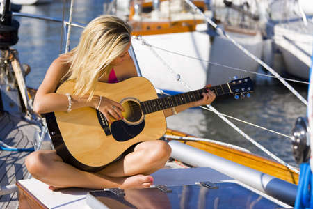 A beautiful young blond woman sitting on the deck of a boat playing her guitar