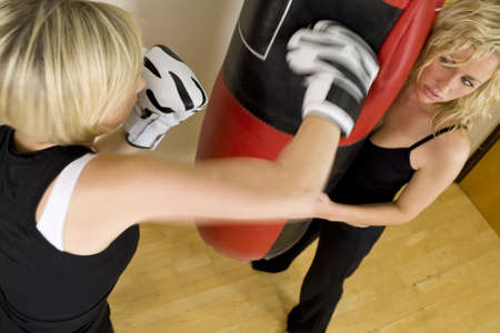 punching bag: Motion blurred shot of two beautiful young women working out on a punch bag in a boxing gym Stock Photo