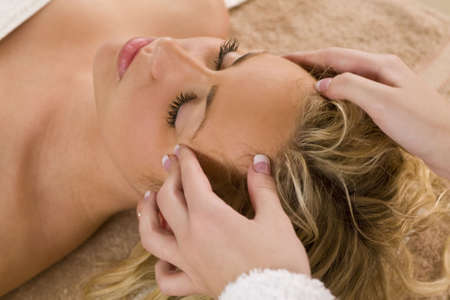 contented: A young blond woman receiving a relaxing head massage from a beauty therapist Stock Photo