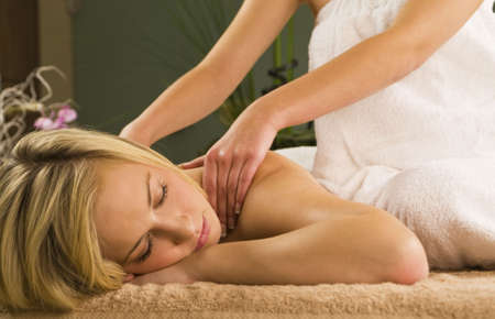 A young woman relaxing at a health spa while having a massage Stock Photo - 2340200