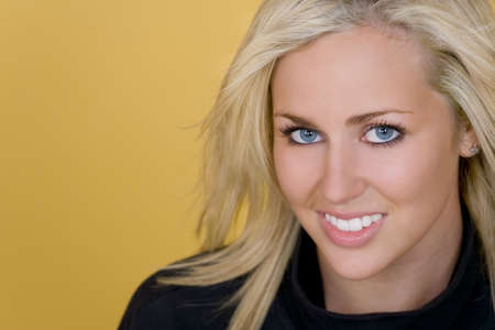 Studio shot of a beautiful young blond woman with bright blue eyes looking happy Stock Photo - 2358150