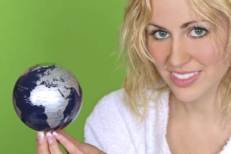 A beautiful young woman with green eyes holds a globe in balance - shot with a green background that could be used to convey green issues or relatively easily separated and replaced  photo