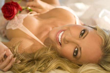 ropa interior femenina: Una mujer rubia hermosa que pone en una cama que agarra una rosa roja y que parece feliz