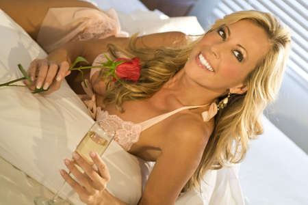 A beautiful blond woman laying on a bed clutching a red rose drinking champagne and looking happy