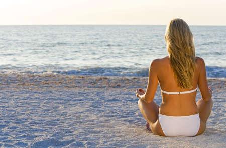 A beautiful young blond woman wearing a white bikini sitting cross legged on a beach at sundown Stock Photo - 2559003