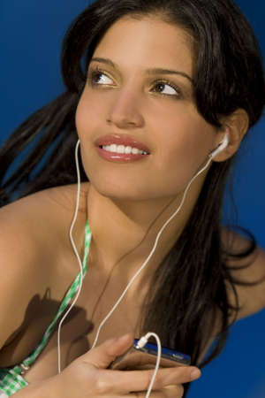 A beautiful young Hispanic woman in a bikini listening to her mp3 player photo