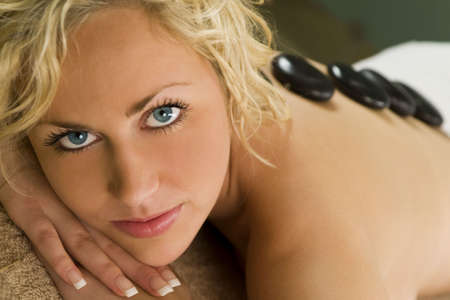 A beautiful young blond woman happily smiles for the camera as see receives a hot stone massage photo