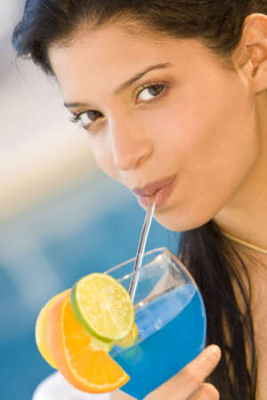 A beautiful young Hispanic woman drinking a cocktail with a swimming pool in the background photo