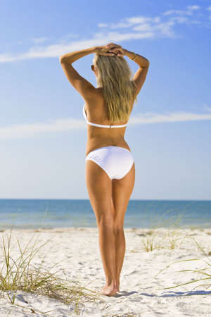 A beautiful young blond woman wearing a white bikini looks out to sea across a beautiful sandy beach