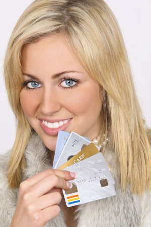 A beautiful young blond woman dressed in (fake) fur and holding a handful of credit card