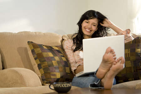 A beautiful hispanic girl relaxing at home drinking cappuccino and using her laptop.