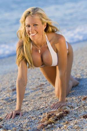 beach breast: A beautiful bikini clad blond woman crawls up a beach in golden sunlight