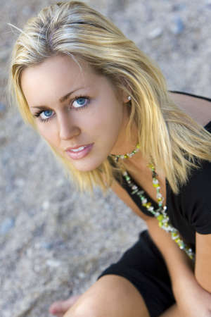 blonde blue eyes: Portrait of a beautiful young blond woman sitting on a beach