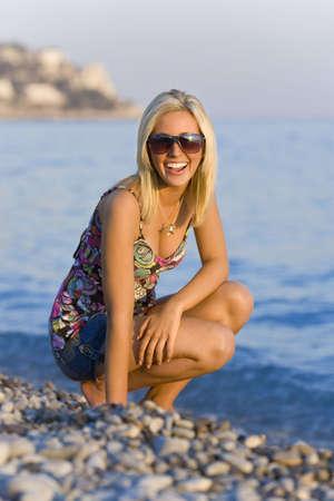 Una mujer rubia joven hermosa en una playa en el resplandor de la tarde como el sol va abajo Foto de archivo