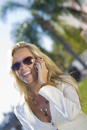 A beautiful young blond woman on the phone in a sunny location backed by palm trees Stock Photo - 2671895