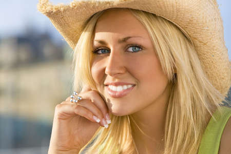 Portrait of a stunningly beautiful young blond woman wearing a straw cowboy hat and bathed in sunshine Stock Photo - 2671897