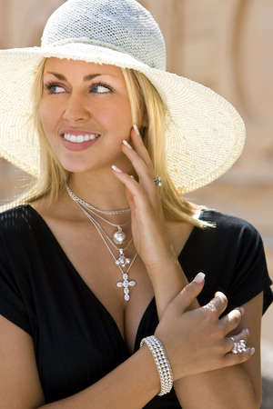 A classy, beautiful young blond woman wearing a sun hat , smiling and wearing a black dress and silver jewelry