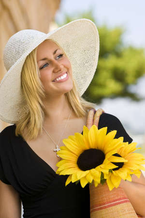 sun hat: A beautiful young blond woman wearing a sun hat and smiling while carrying a shopping bag of sunflowers