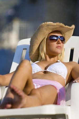 cappello cowboy: Una bellissima giovane donna bionda in occhiali da sole e cappello cowboy rilassa sotto il sole di mare  Archivio Fotografico