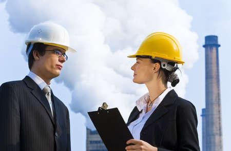 lluvia acida: Los j�venes hombres y mujeres los administradores que trabajan juntos en una situaci�n industrial con