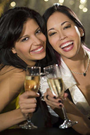 Two attractive young women, one Asian one Hispanic, enjoying champagne in a nightclub