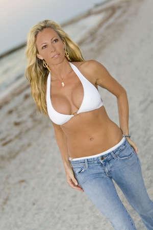 beach blond hair: A beautiful young blond woman wearing a white bikini top and jeans walks along a beach at sundown Stock Photo