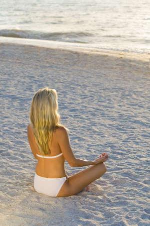 Una hermosa mujer joven rubia que llevaba un bikini blanco sentado piernas cruzadas en una playa a la puesta del sol  Foto de archivo
