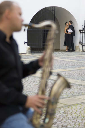 A street musician playing his saxophone serenades two young lovers photo