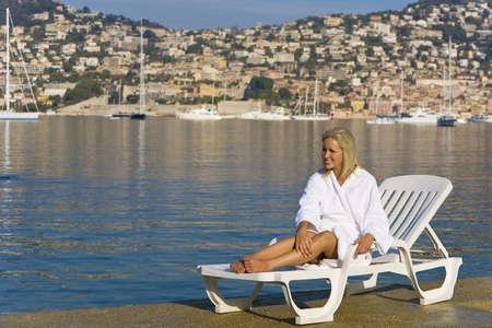 A beautiful young woman sunbathing in a Mediterranean resort photo