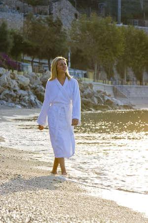 Una hermosa mujer joven caminando por la playa en su túnica como sale el sol  Foto de archivo - 2770429