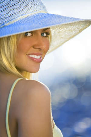Portrait of a stunningly beautiful young blond woman sitting on the beach wearing a hat and bathed in sunshine while the sun glistens off the sea behind her Stock Photo - 2781663