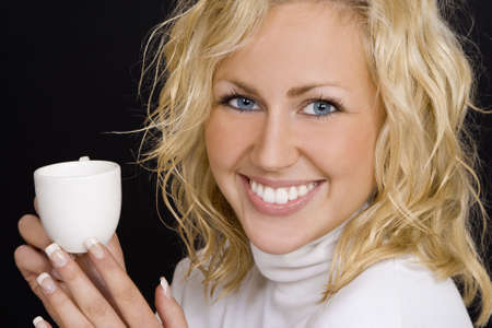 Studio profile shot of a beautiful young blonde woman drinking coffee photo