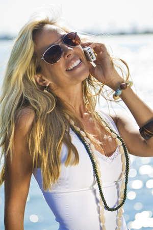 mujer hippie: Una hermosa mujer joven rubia hablando por tel�fono con el sol que refleja frente a la mar detr�s de ella