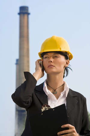 acid rain: A beautiful dark haired woman wearing a hard hat and talking on her mobile phone while standing in front of a factory and its chimneys